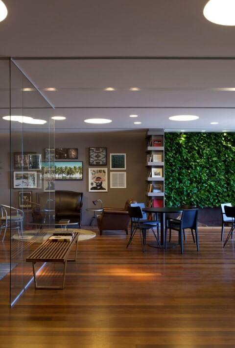 Sala amplo com piso de madeira e jardim vertical Projeto de AMC Arquitetura