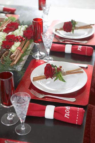 Sousplats vermelhos com pratos brancos em mesa de ceia de natal Foto de Garbo