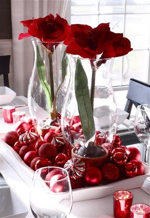 Travessa branca com bolas de natal vermelhas e vasos de vidro com flores na mesa de ceia de natal Foto de White House 51
