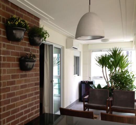 Varanda com jardim vertical em vasos Projeto de Elisa Gali