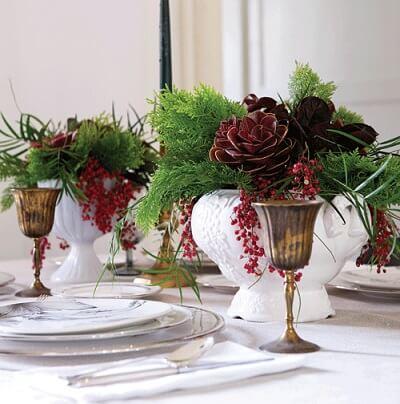 Vasos brancos com plantas falsas em mesa de ceia de natal Foto de Chatelaine
