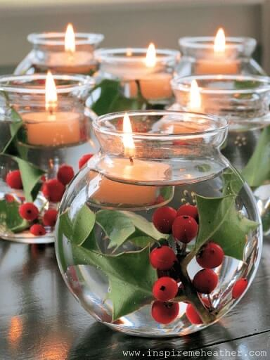 Glass vases with water, plants and candles as Christmas dinner table decoration Photo by Inspire Me Heather