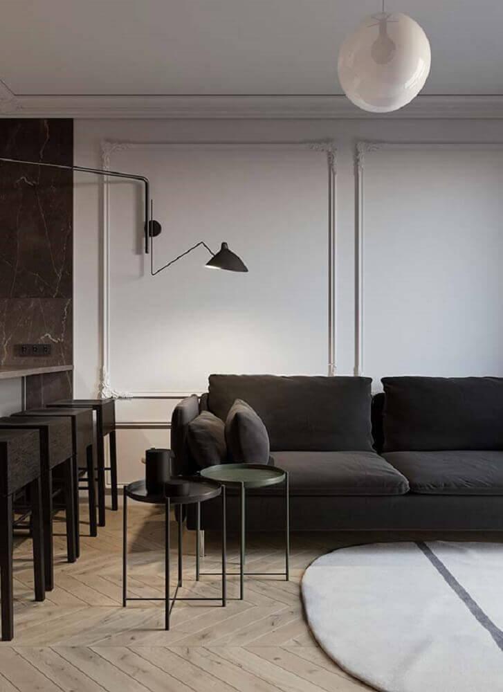 ambiente moderno com boiserie sofá preto e luminária de parede Foto Pinterest