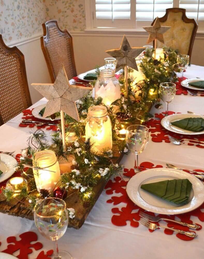 arranjos de natal com velas para decoração de mesa com suporte de madeira ramos de plantas e bolas vermelhas Foto Apsip