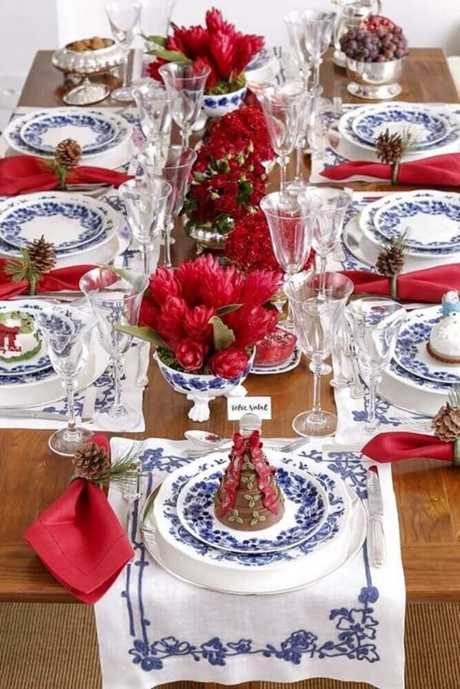 arranjos de natal para mesa decorada com louça azul e branca e flores vermelhas Foto Fashion Submarine