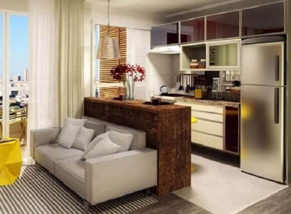 cozinha americana com sala de estar decorada com sofá cinza e bancada de madeira Foto Webcomunica