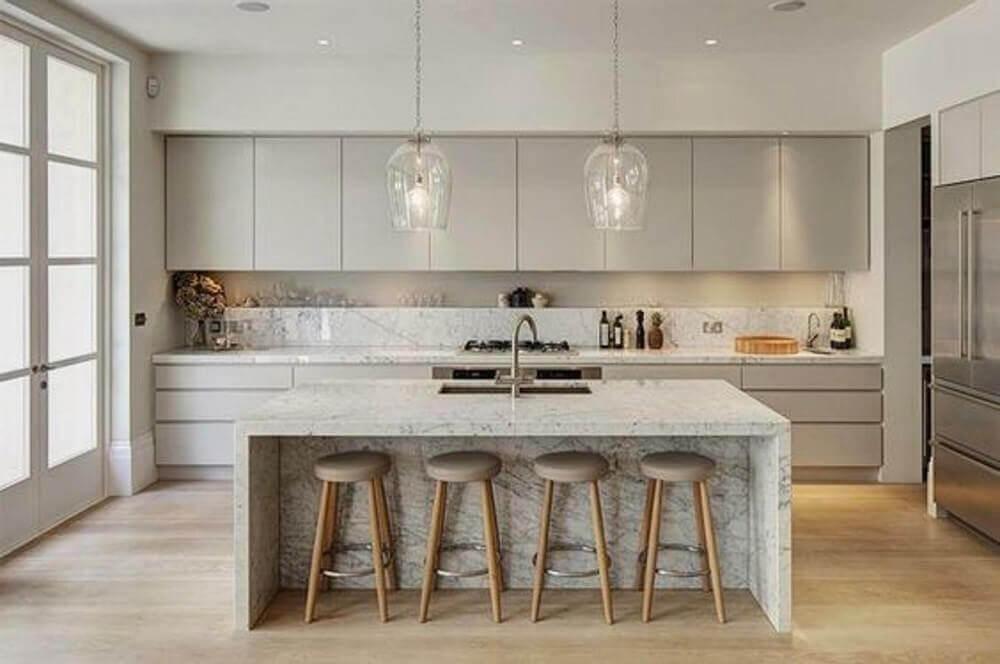 cozinha com ilha decorada com armário de cozinha planejado cinza e pendentes de vidro Foto Mujer Hoy