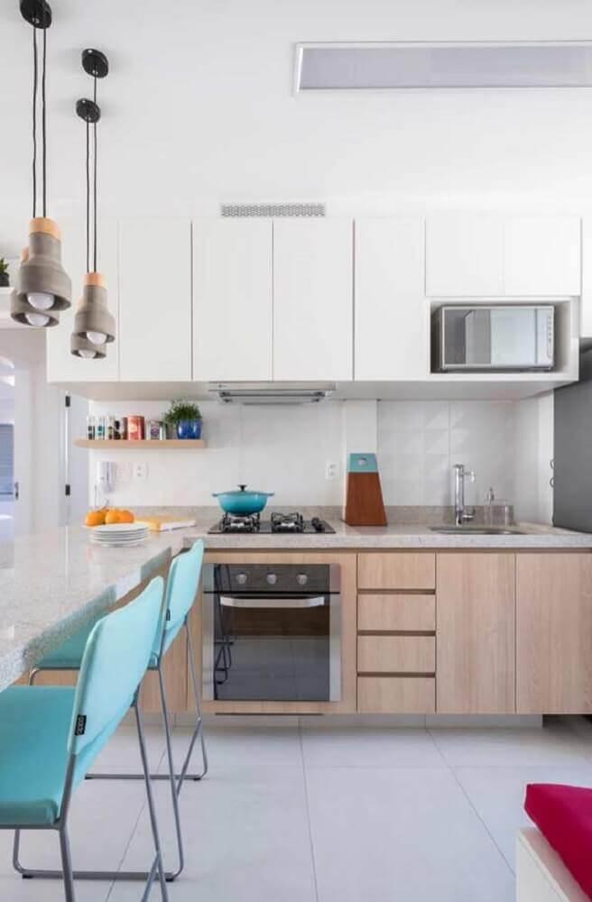 cozinha decorada com pendentes modernos cadeiras azuis e armário de cozinha planejado branco Foto Pinterest