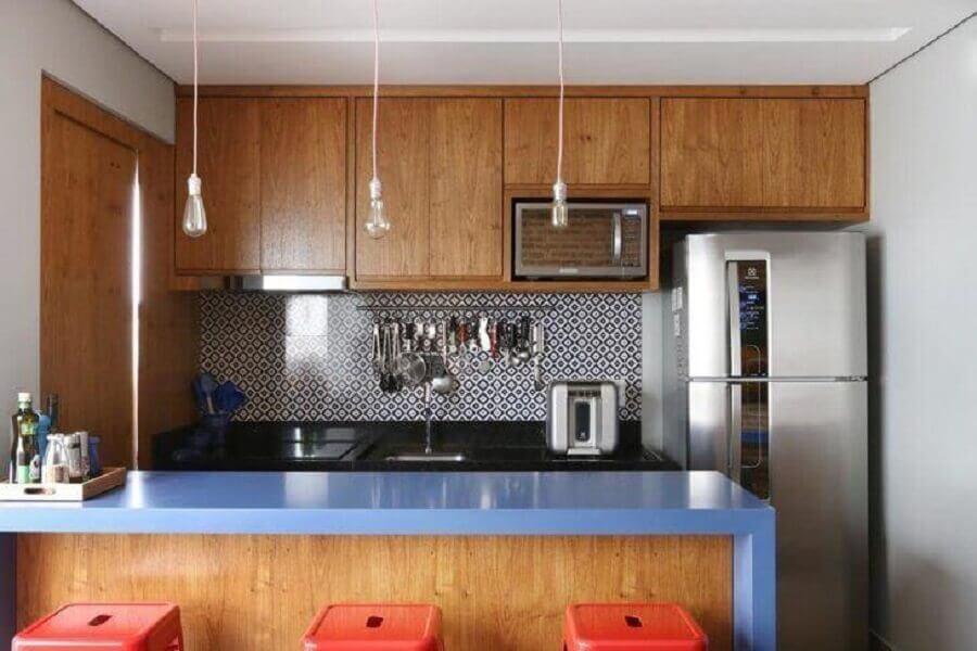 cozinha planejada pequena com balcão azul e armários de madeira Foto GF Projetos