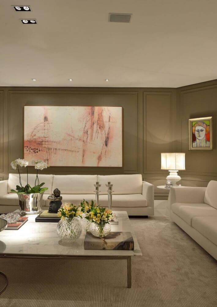 decoração clássica em tons neutros para sala com sofá branco e moldura de parede Foto Marlon Gama