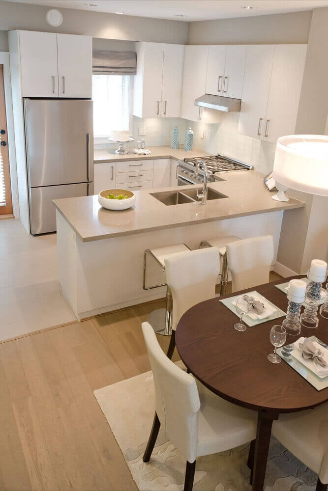 decoração clean para cozinha integrada com sala jantar com cadeiras brancas e mesa de madeira Foto Mi casa revista