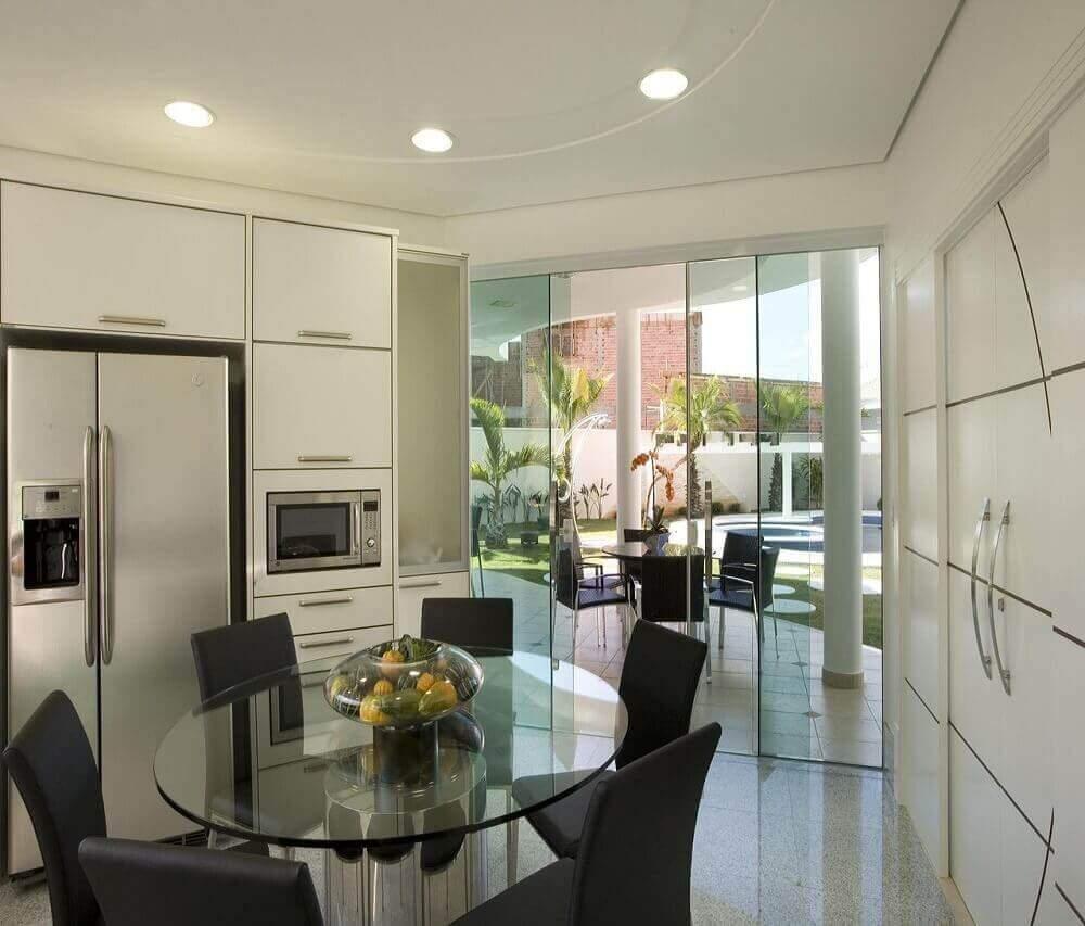 decoração com armário de cozinha planejado todo branco com mesa redonda de vidro Foto The Holk
