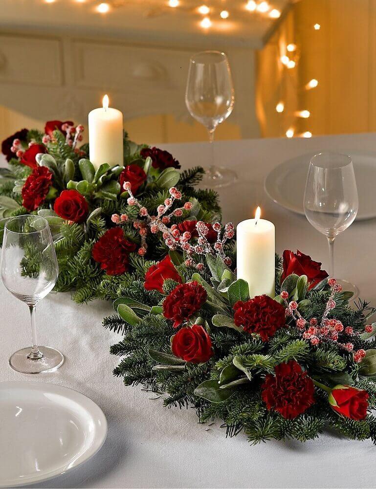 decoração com arranjos de natal com velas e rosas vermelhas Foto Marks & Spencer