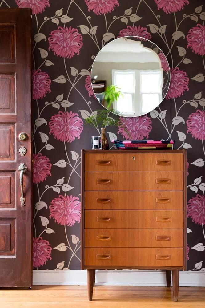 decoração com cômoda de madeira e papel de parede floral rosa com fundo preto Foto Hunker