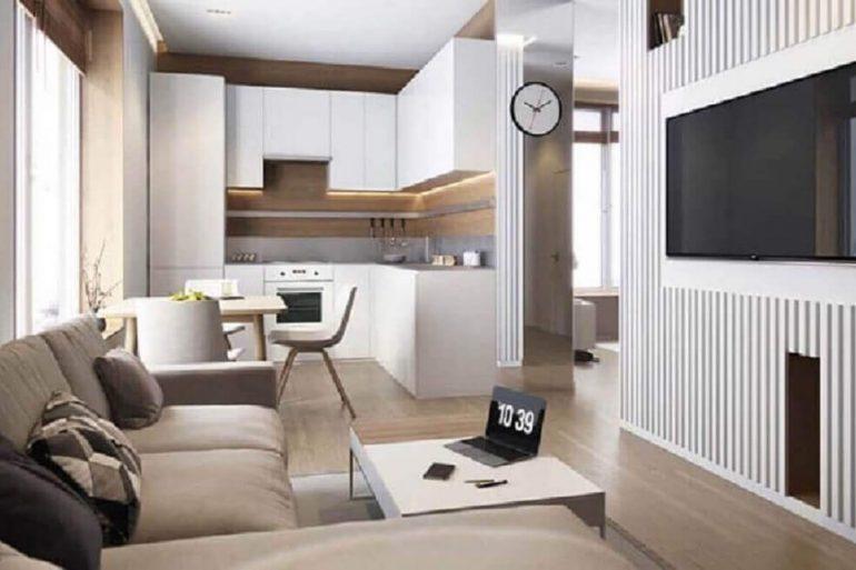 decoração em tons neutros com cozinha planejada integrada com sala de TV
