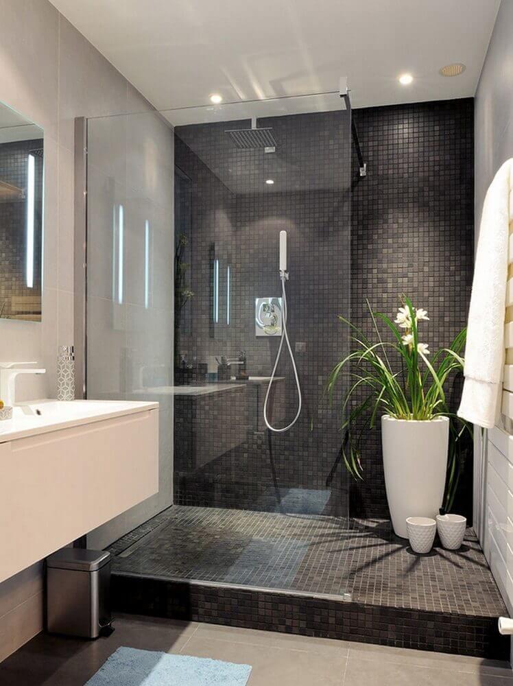 decoração moderna para banheiro com pastilha preta e grande vaso de planta dentro do box Foto Design de Maison