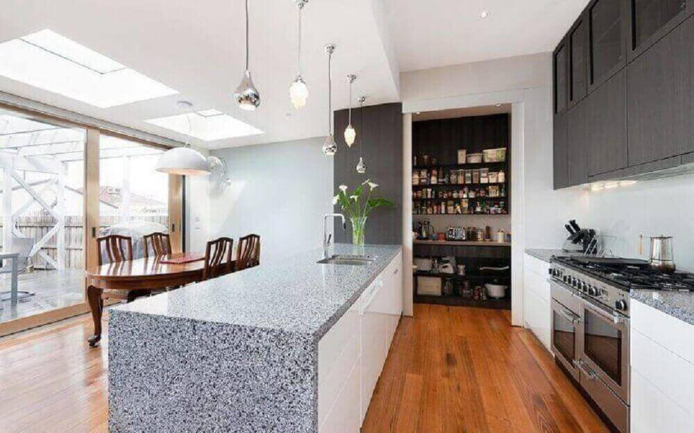 decoração para cozinha integrada com sala de jantar com armário preto mesa de madeira e pendentes prata sobre bancada-de granito Foto Statkus Architecture