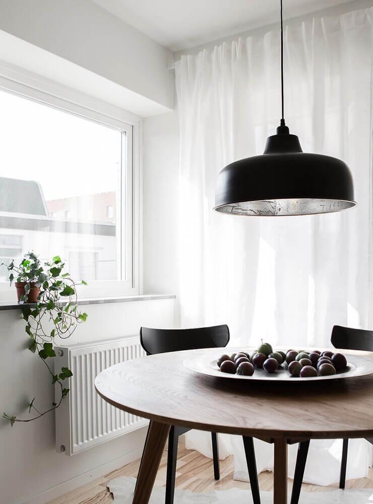 decoração para sala de jantar moderna com mesa redonda de madeira e pendente preto Foto Clark Rassi