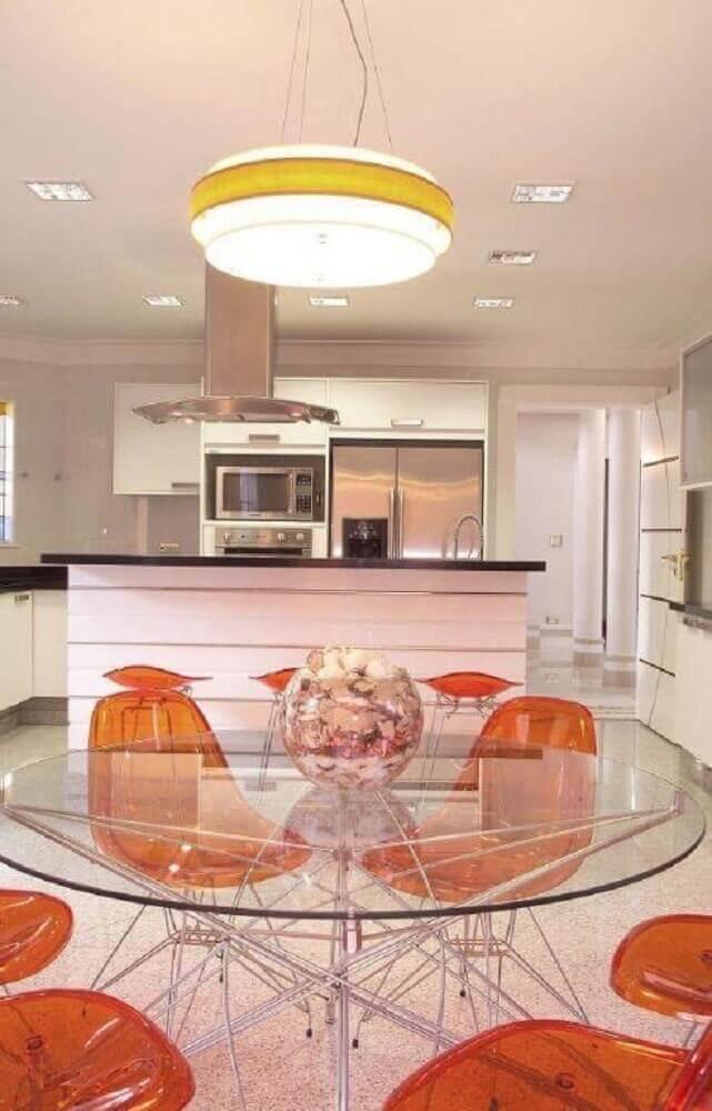 decoração sala de jantar moderna com mesa redonda de vidro e cadeiras de plástico laranja Foto Aquiles Nicolas Kilaris
