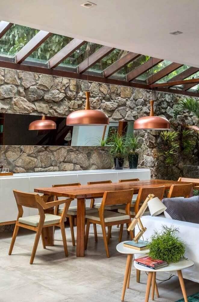 decoração sala de jantar moderna com parede revestida de madeira e pendente cobre Foto The Holk