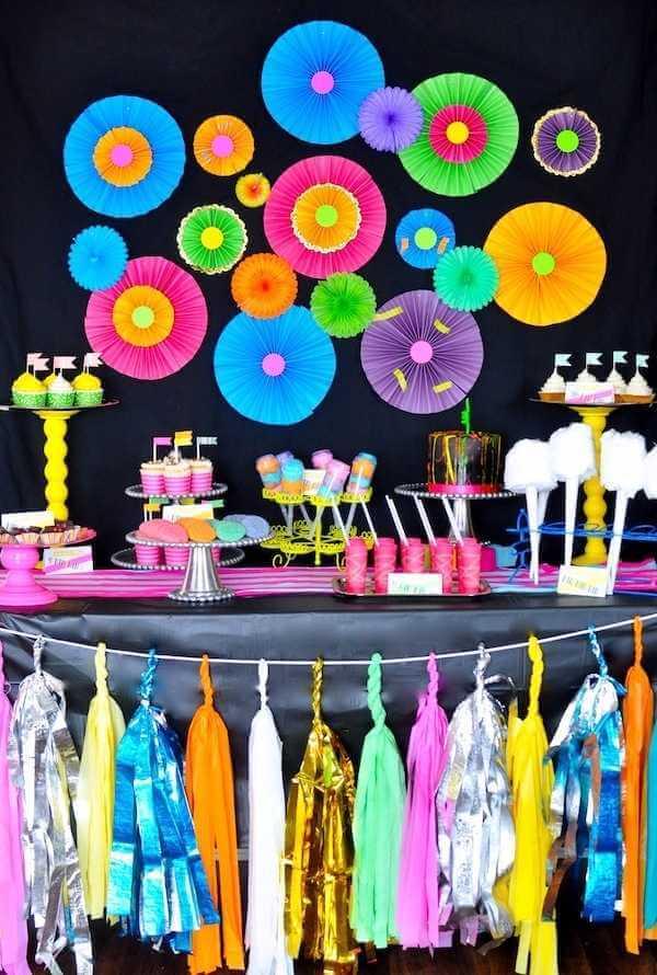 Decoração de festa neon com elementos na mesa de doces