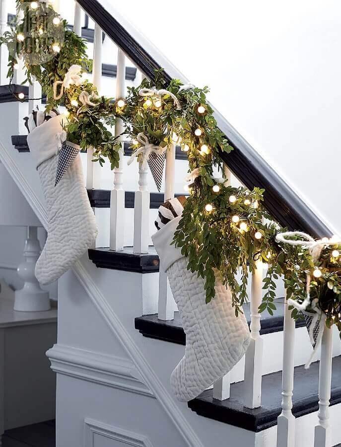 escada decorada com luzes de natal e botas brancas Foto The Grad