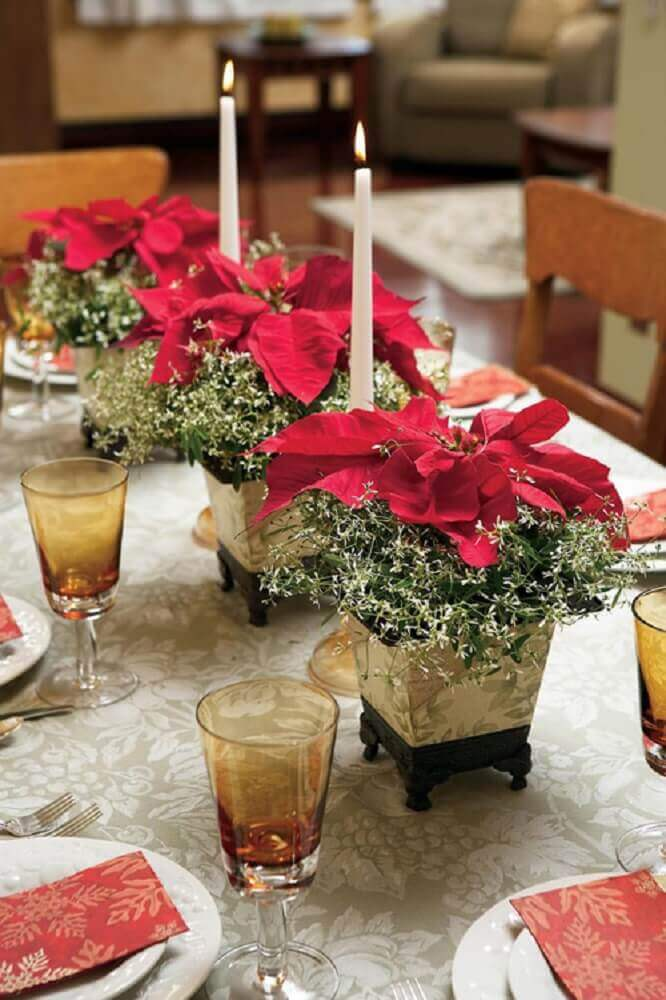 mesa de natal simples decorada com pequenos arranjos de flores vermelhas e velas brancas Foto DanielleMorgan