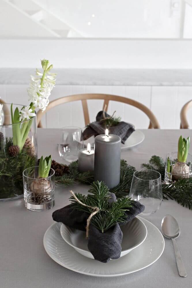 mesa de natal simples e moderna decorada com velas cinzas e ramos de plantas Foto Sweet Harmonie