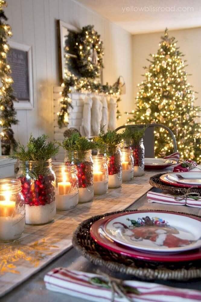 mesa de natal simples e rústica decorada com recipientes de vidro com velas e plantas Foto Seelenflügel