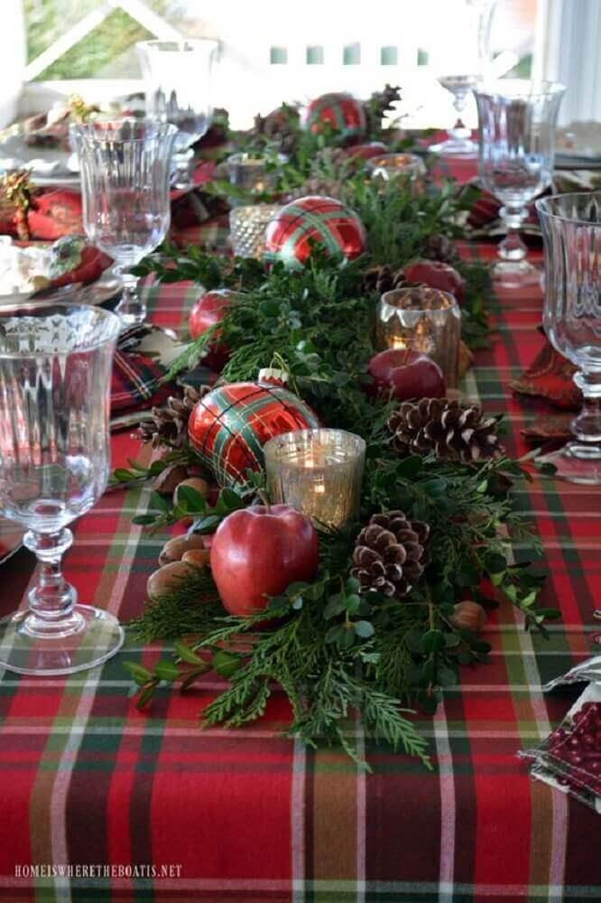 mesa natalina decorada com tolha xadrez e arranjos de natal com ramos de plantas e bolas natalinas Foto Pinterest