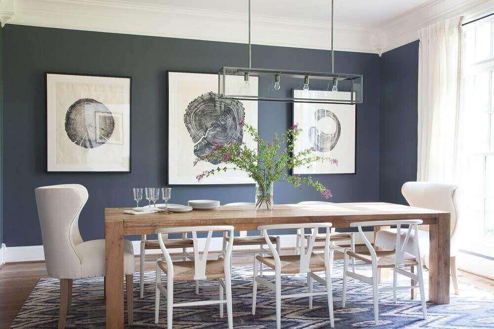 pendente para sala de jantar moderna decorada com tapete cadeiras diferentes e grandes quadros Foto Lonny
