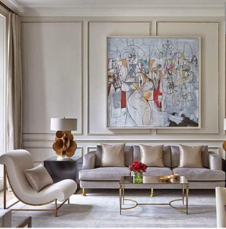 sala de estar decorada com tons neutros poltrona moderna e boiserie com grande quadro Foto Pinterest