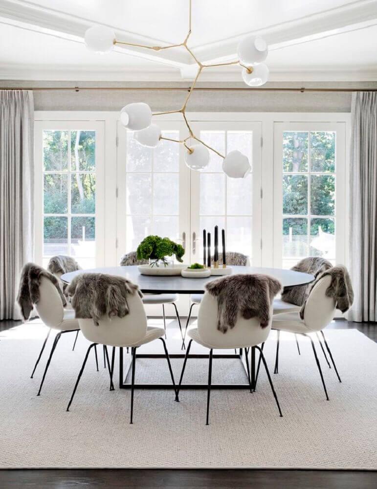 sala de jantar moderna decorada com lustre arrojado e mesa redonda Foto Cpac