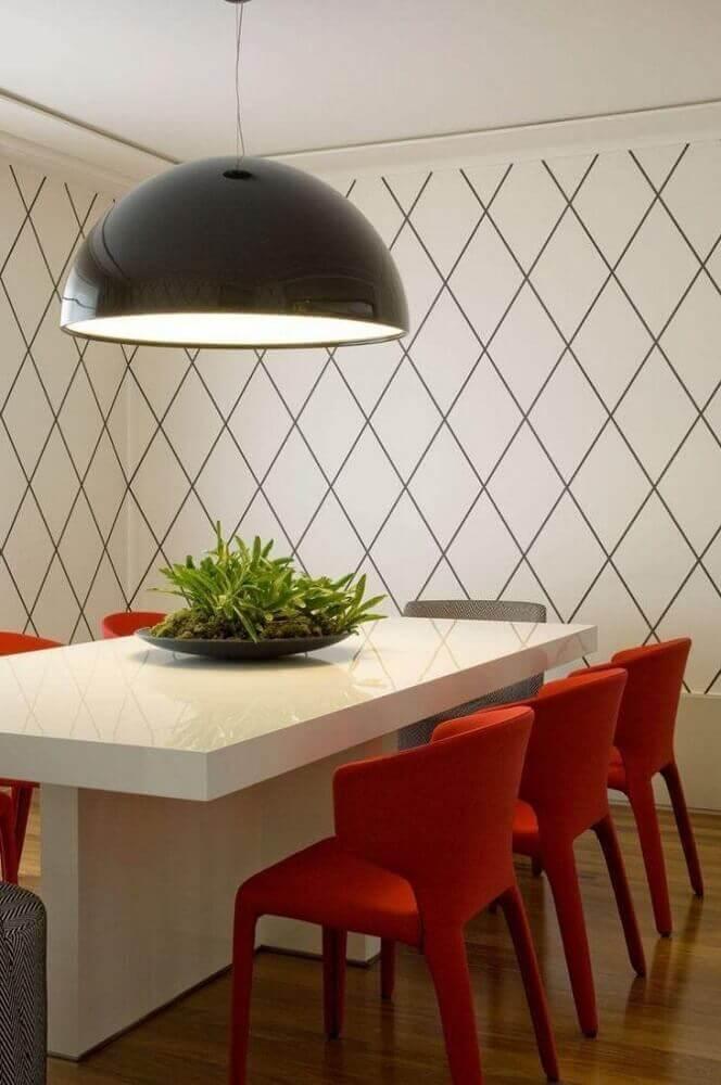 sala de jantar moderna decorada com pendente preto e cadeiras vermelhas Foto Roberto Migotto
