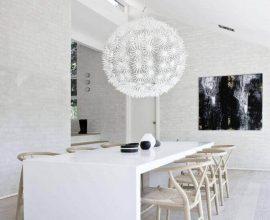 sala de jantar moderna decorada toda branca com grande pendente diferente sobre a mesa Foto Studia 54