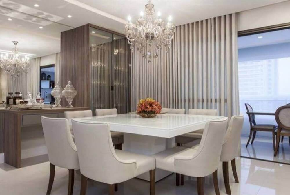 sala de jantar moderna e sofisticada com lustre candelabro e parede espelhada Foto Vanja Maia