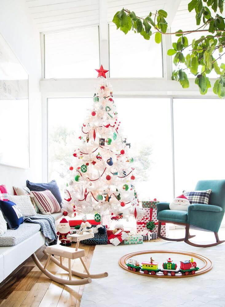 room decorated with white Christmas tree with colorful decorations Photo Emily Henderson