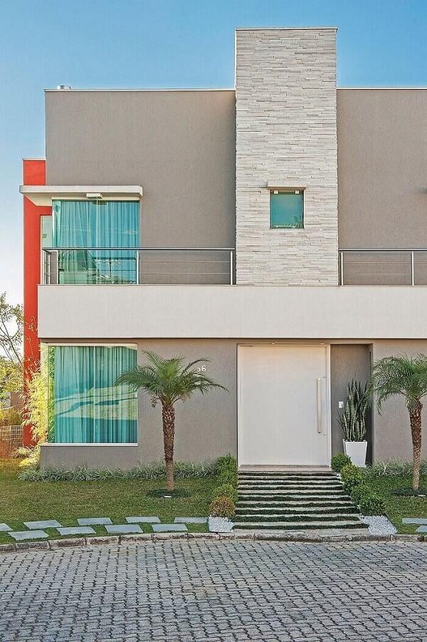 A coluna feita com pedra faz parte do revestimento de parede externa da casa. Projeto por Patrícia Azoni