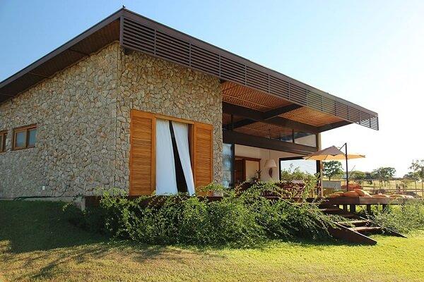 A madeira se conecta perfeitamente com o revestimento de parede externa em pedras. Fonte: Revista Viva Decora