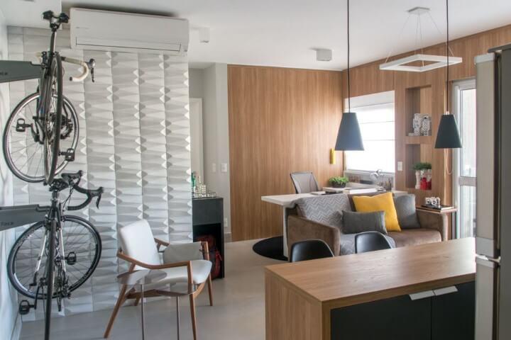 Apartamento pequeno decorado com bancada de madeira do mesmo tom que o revestimento da parede Projeto de Danyela Correa