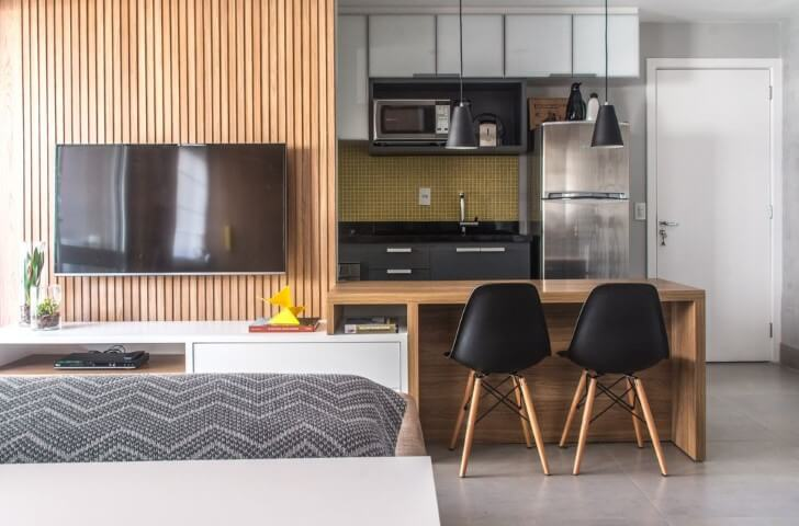 Apartamento pequeno decorado com painel de madeira e cozinha americana Projeto de Danyela Correa