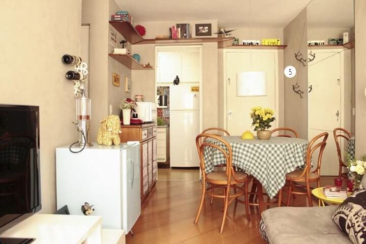 Apartamento pequeno decorado com prateleiras altas na sala integrada Projeto de Casa Aberta