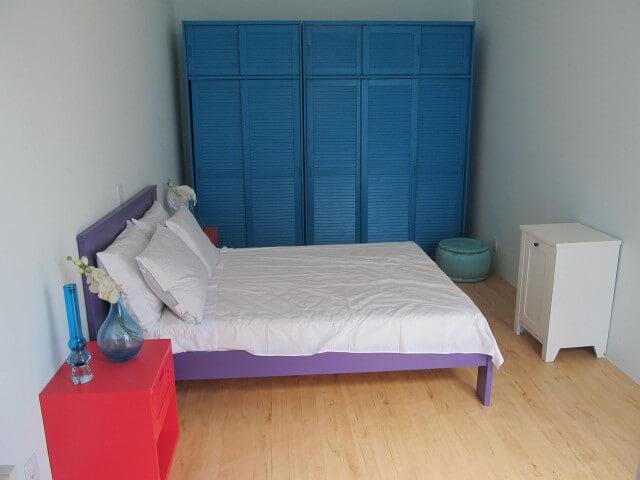 Armário de quarto azul com cama rosa e criado-mudo vermelho Projeto de Brunete Fraccaroli