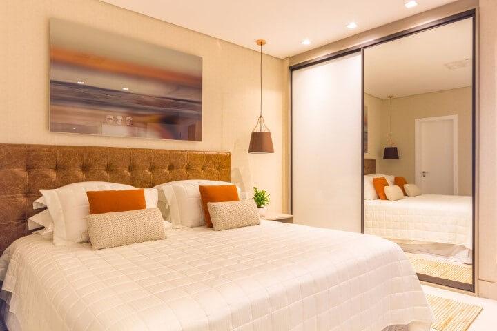 Armário de quarto de casal embutido com portas de correr e espelho Projeto de Patricia Hagobian