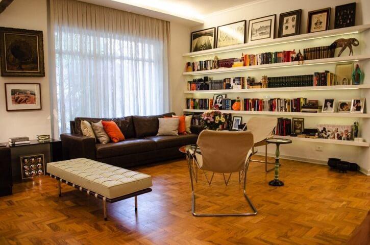 Biblioteca com sofá de couro e piso de taco Projeto de Adriana Fornazari