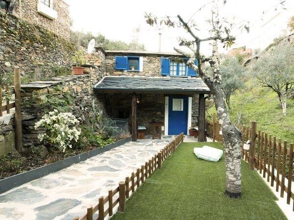 Casa charmosa com portas e janelas em tom azul e revestimento de parede em pedras. Fonte: Revista Viva Decora