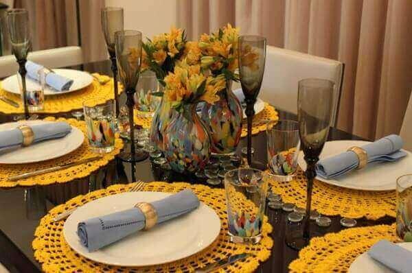 Mesa posta com sousplat amarelo e copos