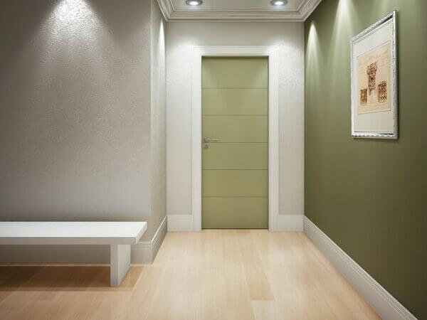 O alizar de 10cm e o rodapé de 15cm destacam a cor verde da porta