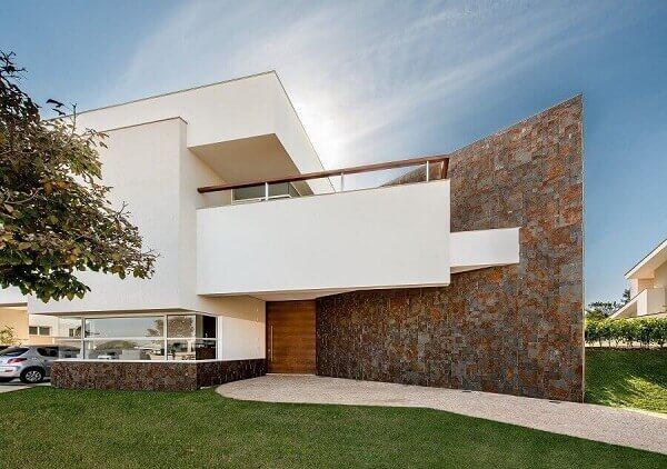 O revestimento da parede externa com pedra ferro traz um contraste interessante ao imóvel. Fonte: Castelatto
