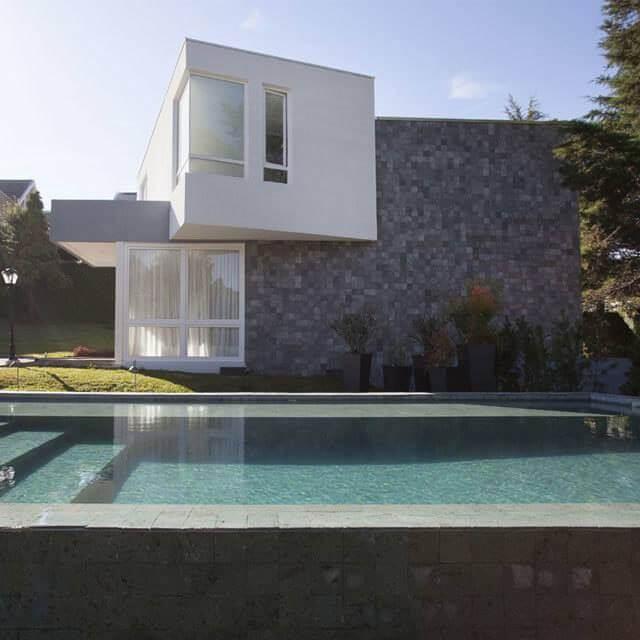 O revestimento de parede externa cinza traz textura para a fachada do imóvel. Fonte: Unlimited Pool
